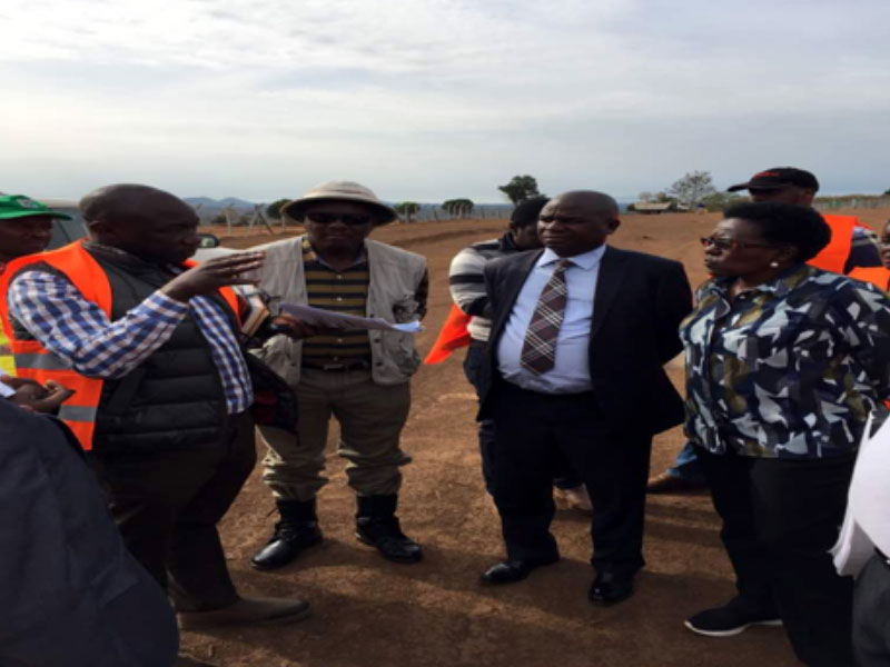 A representative from the construction company explaining the progress of the construction works on the airport at Kabaale Buseruka Hoima to the Minister of state for Bunyoro sub region and the other official from the Ministry of energy and mineral development
